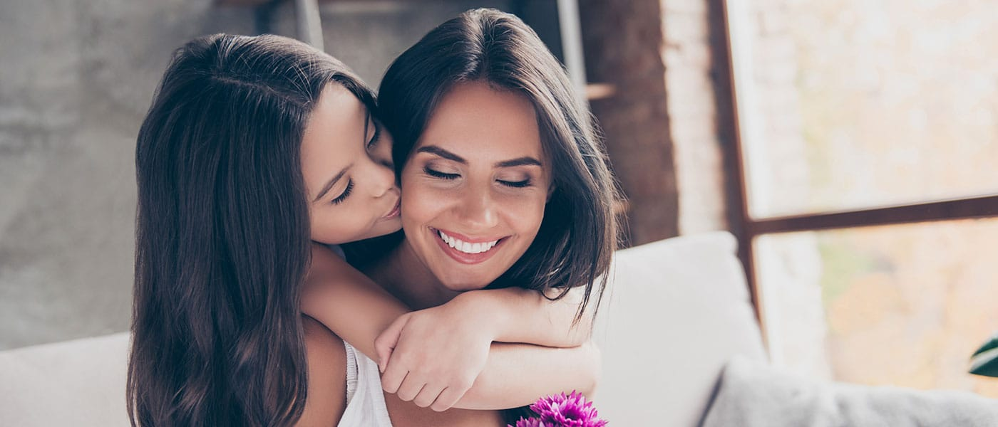 mother daughter connecting and smiling white and brunette latina