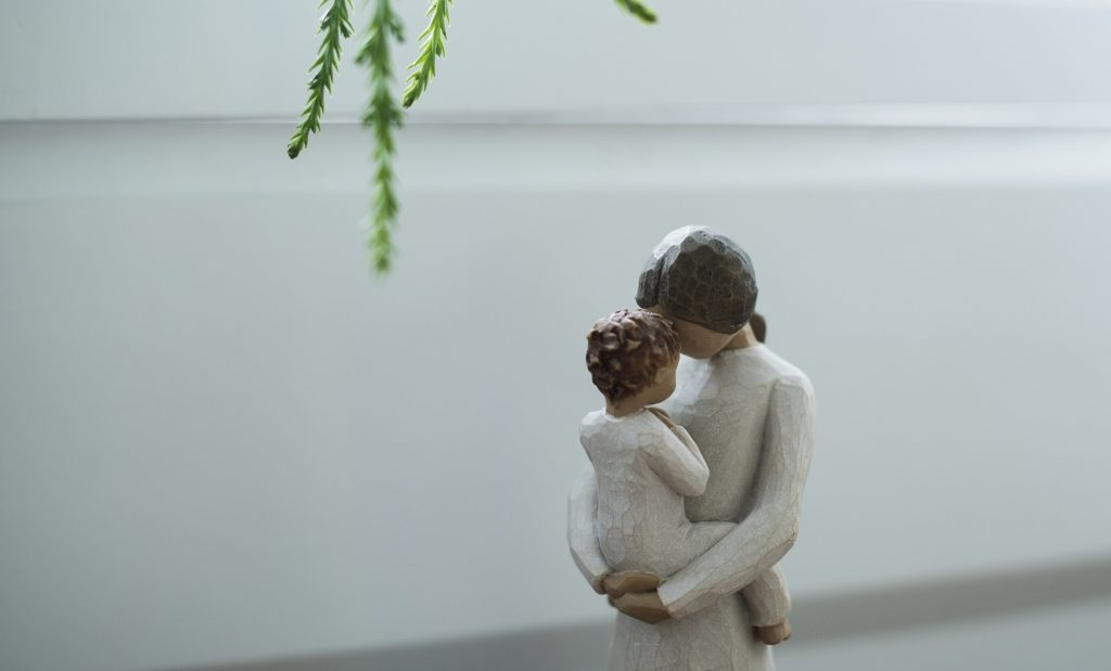 mom remembering_with baby_figurine